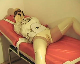 Strapped with medical restraints, hood, latex and... Struggling.